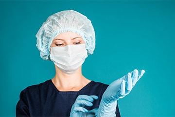 Eine Mitarbeiterin von MI.CA Gebäudereinigung stülpt sich vor einer Desinfektionsreinigung in Heidelberg, Mannheim & Rhein-Neckar-Kreis einen Handschuh über.