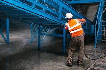 Ein Mitarbeiter von MI.CA Gebäudereinigung reinigt eine Maschine in Heidelberg, Mannheim & Rhein-Neckar-Kreis.